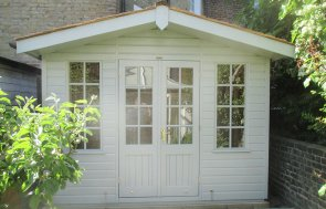 An attractive summerhouse with smooth shiplap cladding painted in a light shade. It has an apex roof covered with cedar shingles, double doors and windows with georgian bars.