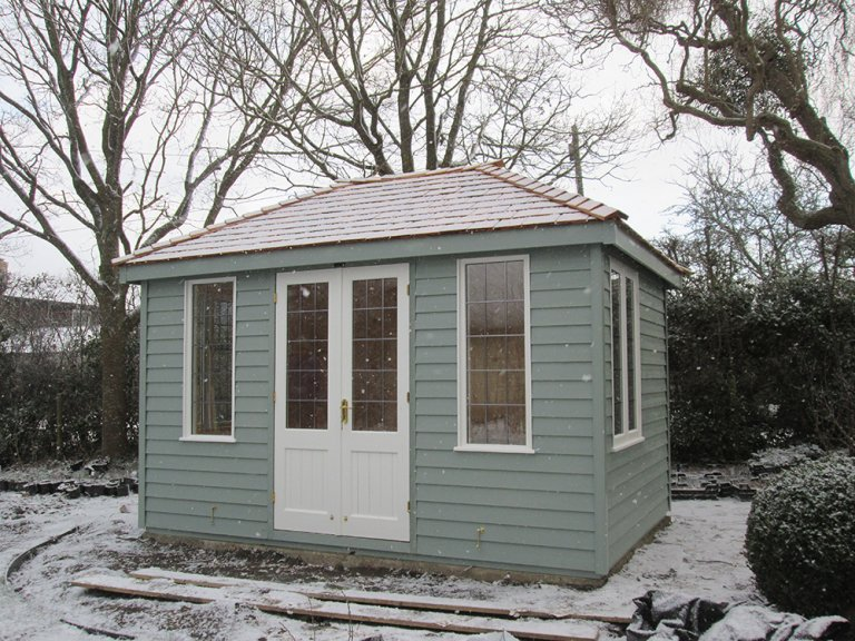 A cley summerhouse pictured in snowy surroundings with a hipped roof and leaded windows. It is clad with weatherboard timber and painted in a two-tone contrasting fashion to the windows and doors.