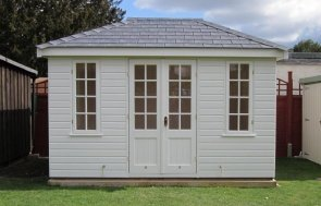 A medium sized summerhouse clad with smooth shiplap cladding and painted in the light exterior shade of sandstone. The double entrance doors are half glazed with leaded windows and there are another few windows on the building that open to allow ventilation.
