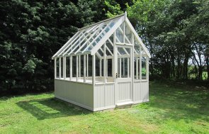 A medium-sized greenhouse situated in a large grassy area with two opening roof vents and smooth shiplap cladding painted in the exterior shade of Twine.