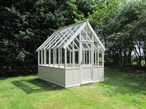 A medium-sized greenhouse situated in a large grassy ar