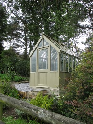 A greenhouse pictured in an attractive location beside woodlands and hedgerows. The greenhouse is a smaller size and features smooth shiplap cladding painted in the exterior shade of Taupe.