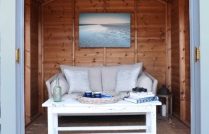An interior shot of the blakeney summerhouse with double doors open and the internal sofa with coffee table visible.