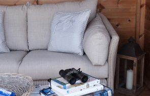 An internal shot of a decorated blakeney summerhouse with a sofa, coffee table, books and bird watching equipment.