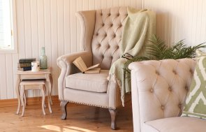 An interior shot of the Cley summerhouse styled as a reading room with a large armchair and sofa, featuring blankets and piles of books with one left open on the chair.