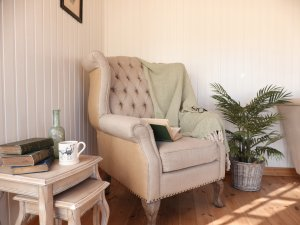 An interior shot of a cley summerhouse styled as a reading room with an armchair. There is a small table with a cup of coffee placed on it and an antique bottle containing fairy lights.