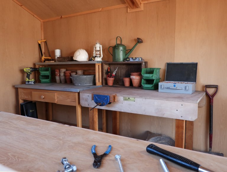 A detailed internal shot of a superior shed with lining and insulation. In the foreground runs the edge of a workbench with tools scattered across the surface. In the background of the picture are two more workbenches covered with tools and various different utensils.