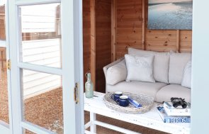 An interior shot of the Blakeney Summerhouse showing its double doors with one open leading into the interior where there is a sofa and coffee table.