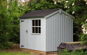 An apex garden shed with traditional features such as a corrugated roof, rustic-cut cladding and georgian bars on the window. It is painted in Painters Grey.