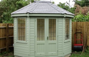 A small summerhouse with a hipped roof and smooth shiplap cladding. It has double door access and opening windows with an attractive slate roof. It is painted in the exterior shade of Lizard.