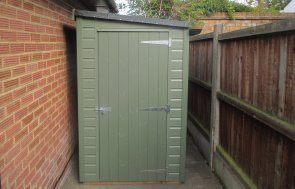 A small shed with a pent roof covered with heavy-duty felt and painted in the shade of Moss