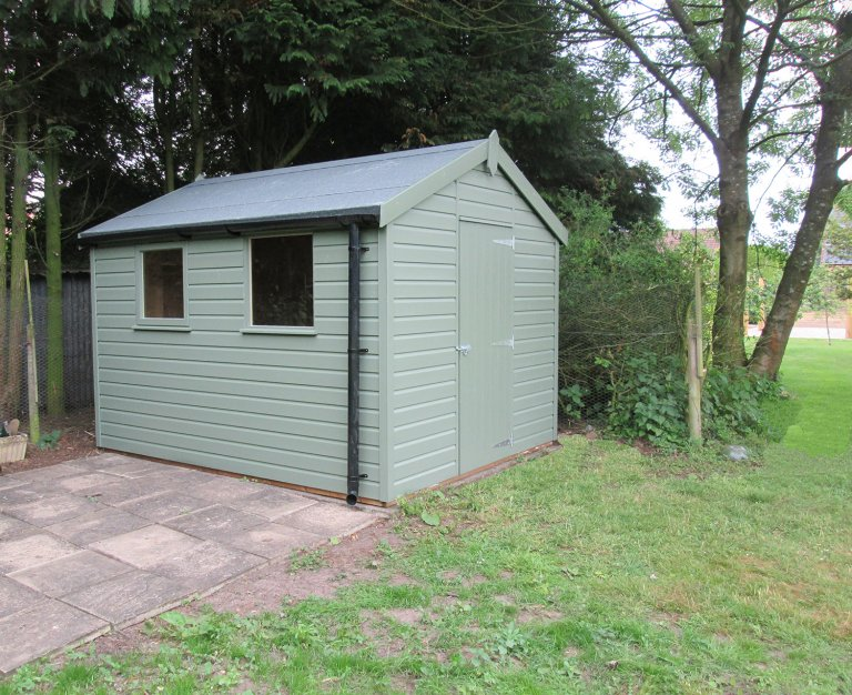 An apex garden shed with black guttering, two fixed windows, a single access door and a felt-covered roof.
