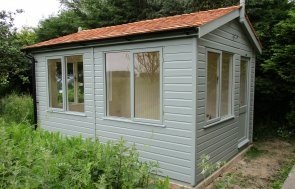 An apex garden studio with cedar shingles on the roof and several desk height windows.