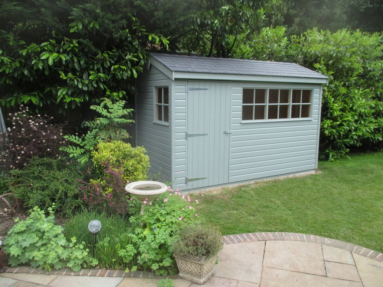 An attractive apex garden shed with shiplap cladding. Nestled in a pretty spot of the garden, the shed features grey slate tiles on the roof and windows with georgian bars.