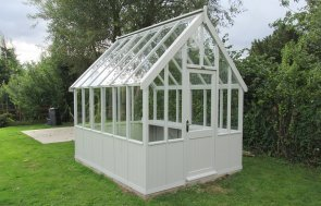 An apex greenhouse with exterior shiplap cladding painted in Pebble, a shade of light grey.