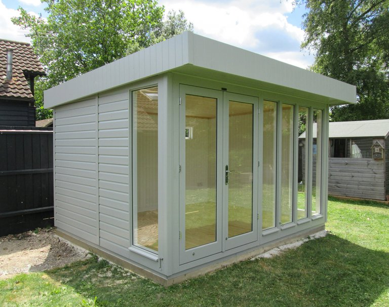 An attractive and modern-looking Garden Studio with a pent roof and smooth shiplap cladding featuring fully-glazed windows and a painted interior.