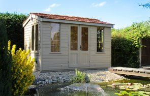 An attractive apex-roof summerhouse with cedar shingles and smooth shiplap cladding. It has double doors and leaded windows and is positioned in front of a lovely pond area.
