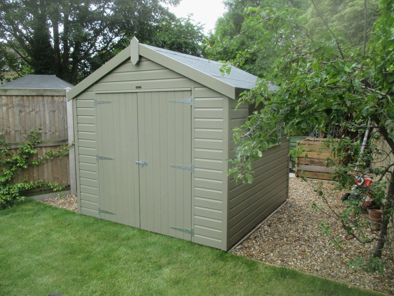 An apex garden shed with double door entry and smooth shiplap cladding painted in Stone
