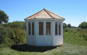 A distinctive and charming summerhouse with an octagonal roof covered in cedar shingles. The smooth shiplap exterior is painted in a Farrow and Ball shade of pointing.