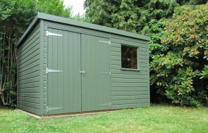 A small garden shed painted an attractive green colour with a pent roof and double doors. There is a small fixed window to the right-hand side of the doors and the exterior is clad with smooth shiplap.