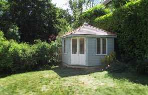 An attractive summerhouse designed to fit into the corner of any outdoor space, sat prettily beside a tall conifer hedge overlooking a grassy lawn. The summerhouse has a distinctive roof covered with cedar shingles and two-tone paint.