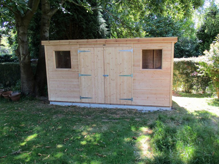 A natural looking garden shed with double doors and two fixed windows either side. It has a pent roof which slopes backwards from the front of the building. The shiplap exterior has been coated with light oak preservative stain which keeps the look of the natural wood