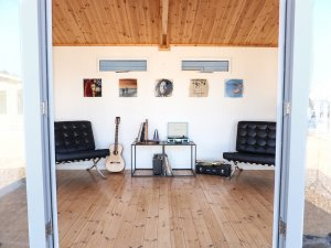 An interior image of the Burnham studio decorated as a music room with seats, cover art and various instruments.