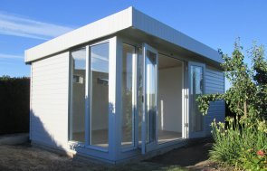 An attractive and contemporary salthouse studio with a pent roof and shiplap exterior cladding painted in the shade of pebble. Modern garden studio hand made in uk.
