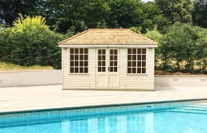 A stunning summerhouse with a hipped roof and georgian windows beside a swimming pool