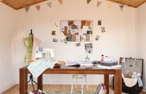 Binham Studio dressed internally as an arts and crafts room with bunting, flags a mannequin and sewing machine. There is a large table covered with sketches and material as well as books and a mood board on the rear wall.