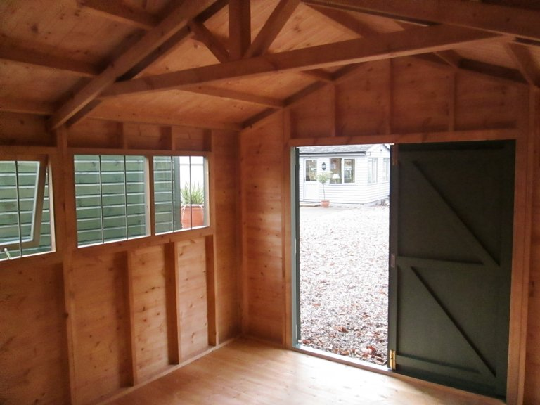 An image showing the interior of a medium sized superior shed. It is an apex building with a visible truss and double doors. One is open and the other is closed so that the exterior paint colour is visible.