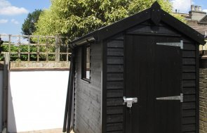 An attractive superior timber garden shed with weatherboard cladding painted in the sikkens preservative stain of black. It has an apex roof and a single fixed window in the length of the small building.