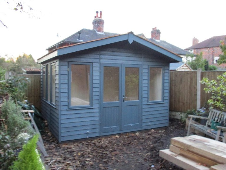 Attractive garden studio with timber weatherboard cladding painted in exterior slate shade. The timber garden building is both insulated and lined with electrics.