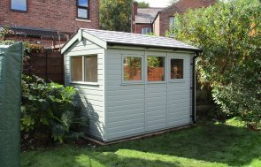 An attractive timber garden shed with apex roof covered in heavy-duty heat-bonded felt. The shed has several opening windows and a single access door in the gable. It is painted in an attractive opaque external paint shade of Sage.