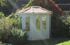 Attractive timber garden summerhouse with leaded windows and an octagonal shape with cedar shingle roof.