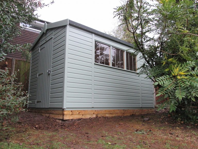 Superior garden shed situated in a customer's garden with trees and shrubbery. The building is clad with smooth shiplap and has a security pack. The high quality timber garden shed is the ideal choice for a busy family garden.
