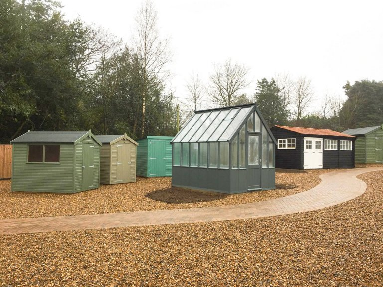 Greenhouse painted in Slate, surrounded by Classic and Superior Sheds