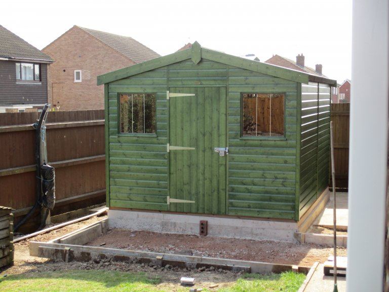 Large garden shed with heavy-duty felt roof and opening windows. Timber shed painted in a green preservative stain.
