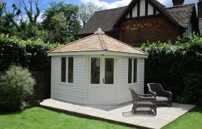 Weybourne Summerhouse in Valtti Cream with weatherboard cladding and a hipped roof with cedar shingle tiles
