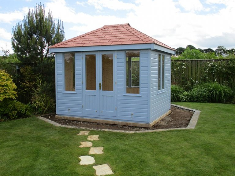 Cley Summerhouse in Sundrenched Blue with a hipped roof covered in our terracotta slate effect tiles