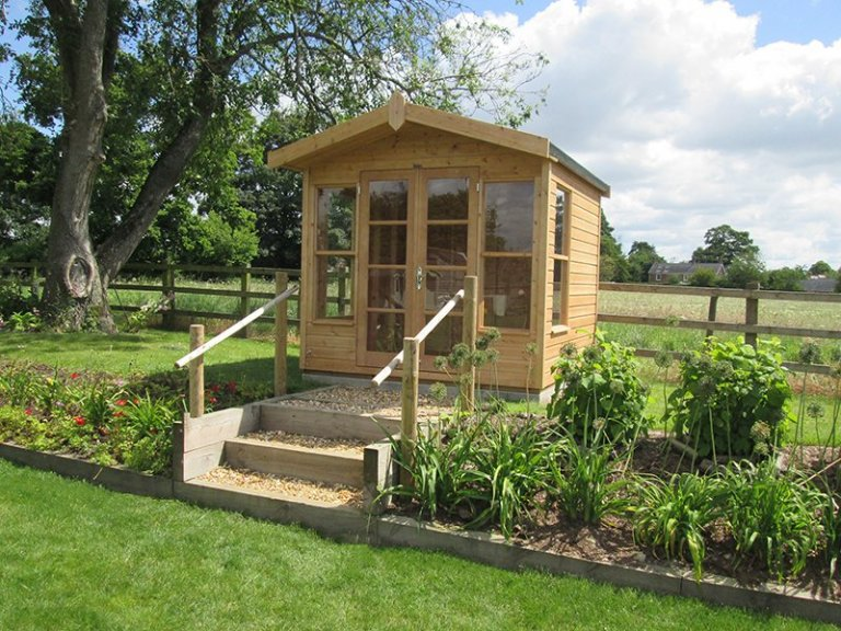 Blakeney Summerhouse with Light Oak Preservative, overhanging heavy duty felted roof and polished chrome door furnishings