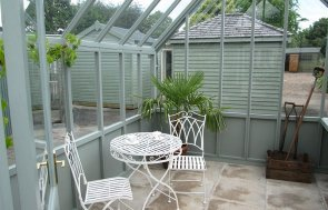 Inside our 3.0 x 3.6m Greenhouse at our Nottingham Show Site with garden table and chair