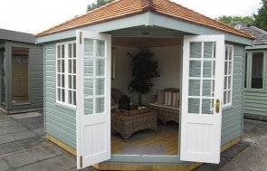 3.0 x 3.0m Weybourne Summerhouse at our Nottingham Show Site with open door in the shade Sage from our exterior paint system