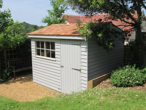 Superior Shed in Pebble with cedar shingle roof tiles and Georgian Windows