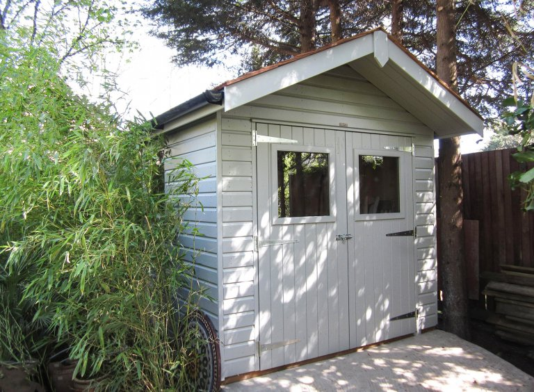 Superior Shed with double doors and a roof overhang painted in Ivory from our exterior paint system