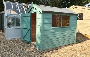 Side view of the 1.8 x 2.4m Classic Shed in Mint at Sunningdale with its door open