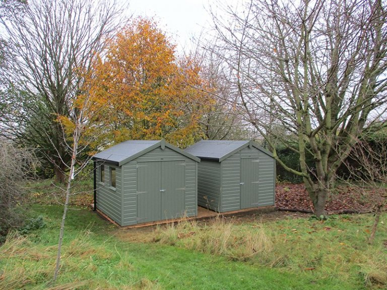 A pair of 2.4 x 3.0m Classic Sheds, both painted in Moss