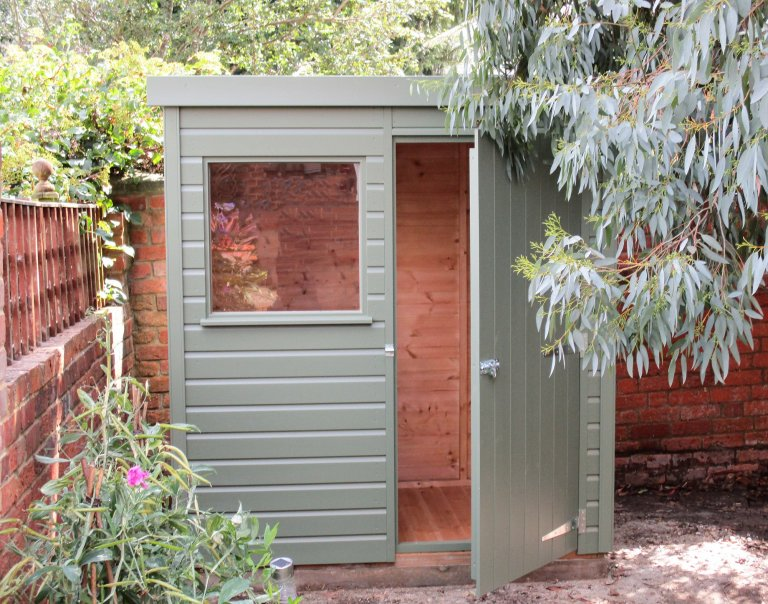 1.2 x 1.8m Classic Shed painted in Moss with a workbench