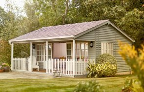6.0 x 6.0m Pavilion Garden Room set in a pretty garden