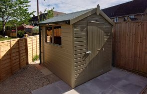 1.8 x 2.4m Classic Shed painted in Classic Stone with an apex roof and guttering